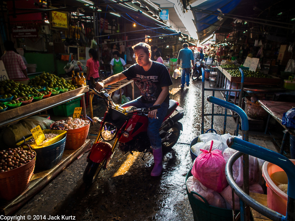 19 NOVEMBER 2014 - BANGKOK, THAILAND: Workers in a lane between market stalls in Khlong Toei Market in Bangkok. Between July and September the economy expanded 0.6 percent compared to the previous year, the National Economic and Social Development Board (NESDB) reported. Thailand's economy achieved a weak 0.2 per cent growth across the first nine months of the year. The NESDB said the Thai economy is expected to grow by 1 percent in 2014. Authorities say the sluggish growth is because tourists have not returned to Thailand in the wake of the coup in May, 2014, and that reduced demand for computer components, specifically hard drives, was also hurting the economy. Thailand is the leading manufacturer of computer hard drives in the world. The Thai government has announced a stimulus package worth $11 billion (US) to provide cash handouts to farmers and promised to speed up budget spending to boost consumption.   PHOTO BY JACK KURTZ