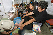 Migrant Francisco reacts as No More Deaths volunteer Heidi Kennedy -a nurse-(left) cleans his blistered foot prior to bandaging at the camp in southern Arizona.