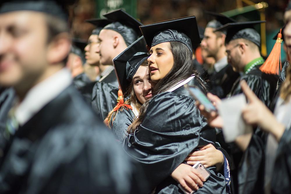 Gabriela Clardke hugs her friend Jennah Rawahneh during fall commencement. Photo by Ben Siegel