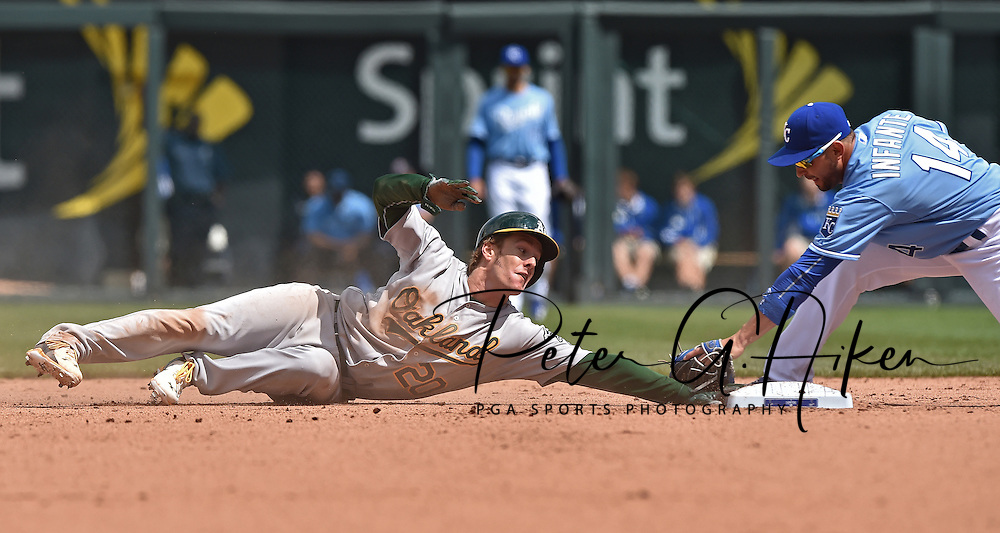Oakland Athletics base runner Mark Canha (20) reaches back for second base before the tag from Kansas City Royals second basemen Omar Infante (14), for a stolen base during the fifth inning at Kauffman Stadium. Mandatory Credit: Peter G. Aiken-USA TODAY Sports