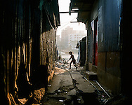 A boy runs through an alley in Karail slum. The slum is estimated to have 200,000 residents, many working in the various industries around the capital.