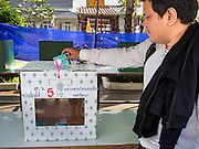 30 MARCH 2014 - BANGKOK, THAILAND:    A man drops his completed ballot into the ballot box at Wat That Thong in Bangkok. Thais voted Sunday to elect 77 senators to the 150-seat Senate. The other 73 senators are appointed by judges and senior officials from agencies such as the National Anti-Corruption Commission (NACC), members of an establishment whom government supporters see as viscerally anti-Thaksin. The government of Yingluck Shinawatra tried to make the senate a fully elected body. That effort was one of the sparks that set off the latest rounds unrest that started in November.   PHOTO BY JACK KURTZ