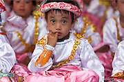 Young Novice Monk with finger in mouth at Novitation Ceremony