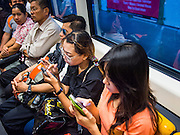"21 AUGUST 2013 - BANGKOK, THAILAND:    Commuters on the Bangkok Skytrain Sukhumvit Line ride to work. Thailand entered a ""technical"" recession this month after the economy shrank by 0.3% in the second quarter of the year. The 0.3% contraction in gross domestic product between April and June followed a previous fall of 1.7% during the first quarter of 2013. The contraction is being blamed on a drop in demand for exports, a drop in domestic demand and a loss of consumer confidence. At the same time, the value of the Thai Baht against the US Dollar has dropped significantly, from a high of about 28Baht to $1 in April to 32THB to 1USD in August.    PHOTO BY JACK KURTZ"