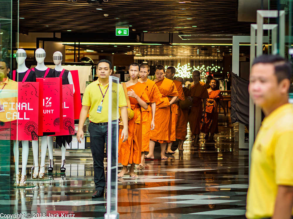 26 JULY 2018 - BANGKOK, THAILAND: Buddhist monks file out of Siam Discovery shopping mall before a merit making ceremony in the Pathumwan area of Bangkok to honor Thai King His Majesty King Maha Vajiralongkorn Bodindradebayavarangkun, also known as Rama X, for his 66th birthday. The King's birthday is 28 July, and events are scheduled throughout Thailand to honor His Majesty. The Pathumwan merit making was organized by businesses in the area.      PHOTO BY JACK KURTZ