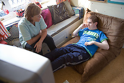 Teenage boy with Autism watching television with his carer,