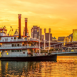 Panorama photo of Cincinnati skyline and riverboat at sunset at night along the Ohio River including Great American Insurance building, Great American Ball Park, US Bank Arena, Scripps building, and PNC Tower building. Panorama photo ratio is 1:3.