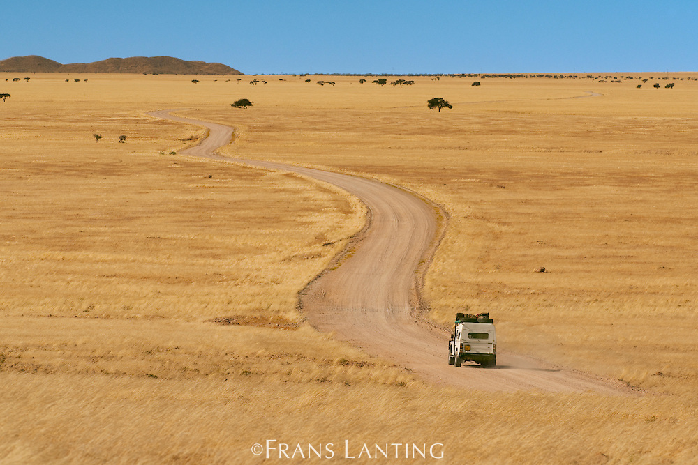 Safari vehicle driving along dirt road, Namib-Naukluft National Park, Namibia