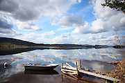 A rowing boat lies on the banks of the Swedish river Angermanaelv in spring.