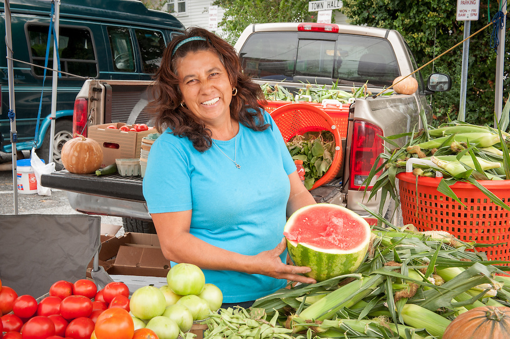 A Hispanic woman shows off a watermelon and other produce for sale at a farmer's market on Maryland's Eastern shore.