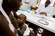 Kouadio Ahou Viviane breast feeds her 16-month-old boy Emmanuel Ngora Kwame during a consultation with Sister Pauline Kangah Akissi and Dr. Charles Joseph Diby (not seen) at the NDA health center in Dimbokro, Cote d'Ivoire on Friday June 19, 2009.