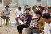 The co-operative farmers in discussion during a workshop delivered by VSO volunteer Giovanni Villafuerte outside the Banan rice warehouse to help them increase their crop yields.  The VSO / Accenture IMA4P project, Banan, Cambodia.