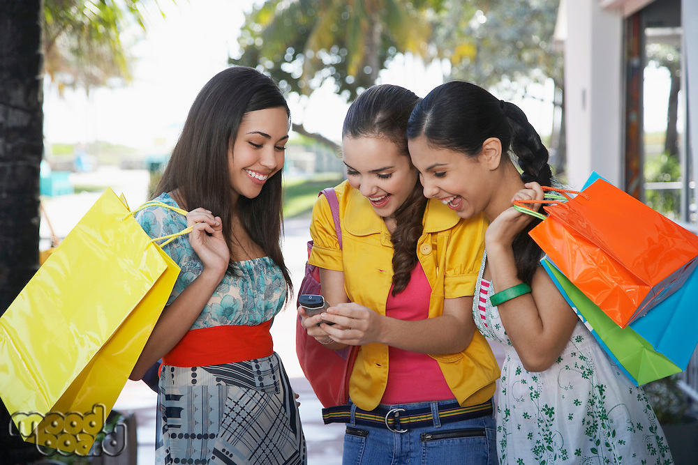 Three teenage girls (16-17) on street holding shopping bags and text messaging