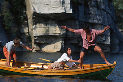 Three people in a rowboat playing around