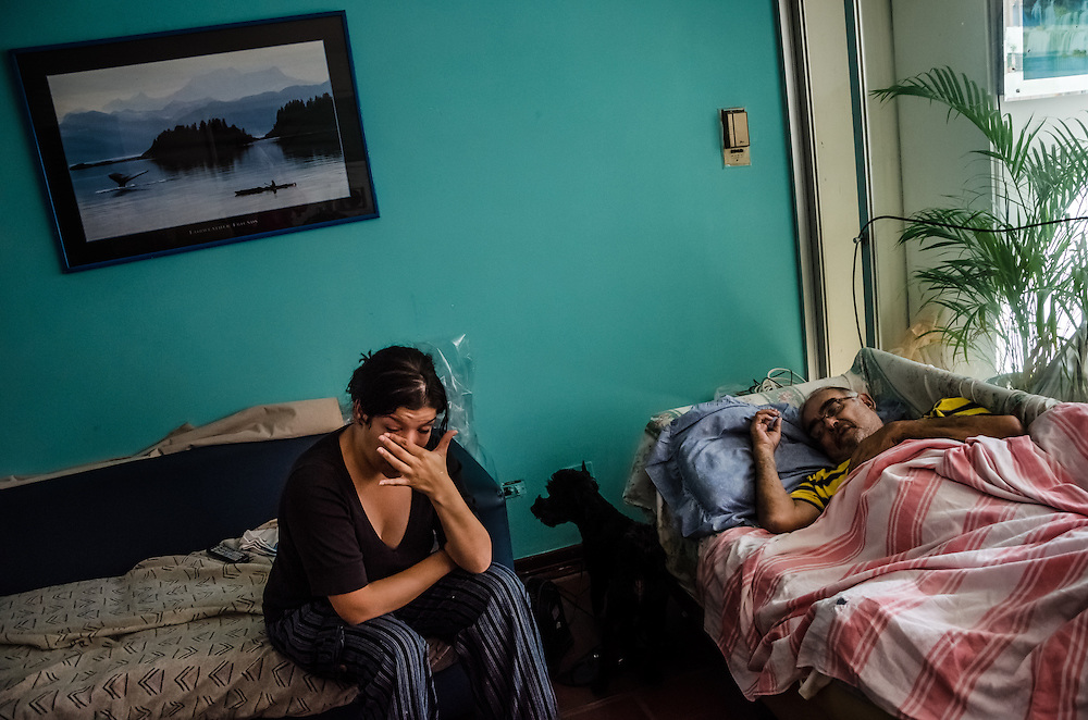 CARACAS, VENEZUELA-JANUARY 22, 2015: Carolina Montoya, 30, cries as she talks about how difficult it is for her to find the medicines prescribed for her father, Ignacio Ortiz, 72, who suffers from a heart condition and needs several difficult to find pills, including Digoxina,  that she has not been able to find for 3 months. She said sometimes, she has to pay a bribe to workers under-the-table at the government-run socialist pharmacy to  sell her hard to find medicines, or buy them on the blackmarket for 4,000 bolivares for a months supply --100 times the official government price, and her entire month's paycheck.  She blames the government for the economic crisis, and subsequent shortages, and believes that if she is unable to find the medicine her father needs, that he will die soon.