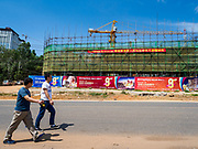 """13 FEBRUARY 2019 - SIHANOUKVILLE, CAMBODIA: Chinese tourists walk by a new Chinese casino under construction in Sihanoukville. There are about 80 Chinese casinos and resort hotels open in Sihanoukville and dozens more under construction. The casinos are changing the city, once a sleepy port on Southeast Asia's """"backpacker trail"""" into a booming city. The change is coming with a cost though. Many Cambodian residents of Sihanoukville  have lost their homes to make way for the casinos and the jobs are going to Chinese workers, brought in to build casinos and work in the casinos.      PHOTO BY JACK KURTZ"""