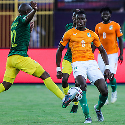 24 June 2019, Egypt, Cairo: Ivory coast's Wilfried Zaha and South Africa's Kamohelo Mokotjo battle in action during the 2019 Africa Cup of Nations Group D soccer match between South Africa and Ivory coast at Al-Salam Stadium. <br /> Photo : PictureAlliance / Icon Sport