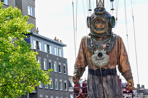 Nederland, Leeuwarden, the Netherlands,  17-8-2018 In het kader van Leeuwarden culturele hoofdstad van europa trokken drie reuzen van het Franse theatergezelschap Royal de Luxe door Leeuwarden, Ljouwert . De duiker is 11 meter hoog, het meisje 5 en de hond 3 . De poppen worden als marionetten bewogen door mensen, lakeien, die aan touwen hangen of trekken . Een muziekgroep op een wagen rijdt erachter .A marionette of French streettheatre Royal de Luxe parades through the streets in the european capital of culture 2018, Leeuwarden.  It presents a new story based on the saga of the Giants called Grand patin dans la glace and is one of three giants. The others are the girl and the dog.Foto: Flip Franssen