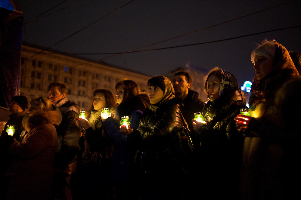 KIEV, UKRAINE - February 22, 2014: People in Maidan pray in memory of the anti-government protestors killed during violent clashes with the Ukrainian elite forces in central Kiev. CREDIT: Paulo Nunes dos Santos