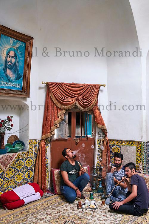 Iran, Province d'Ispahan, Kashan, bazaar, jeunes iraniens fumant du narguilé dans une Tchaikhana, maison de thé // Iran, Isfahan province, Kashan city, bazaar, Iranian men smoking a water pipe in a teahouse, tchaikhana