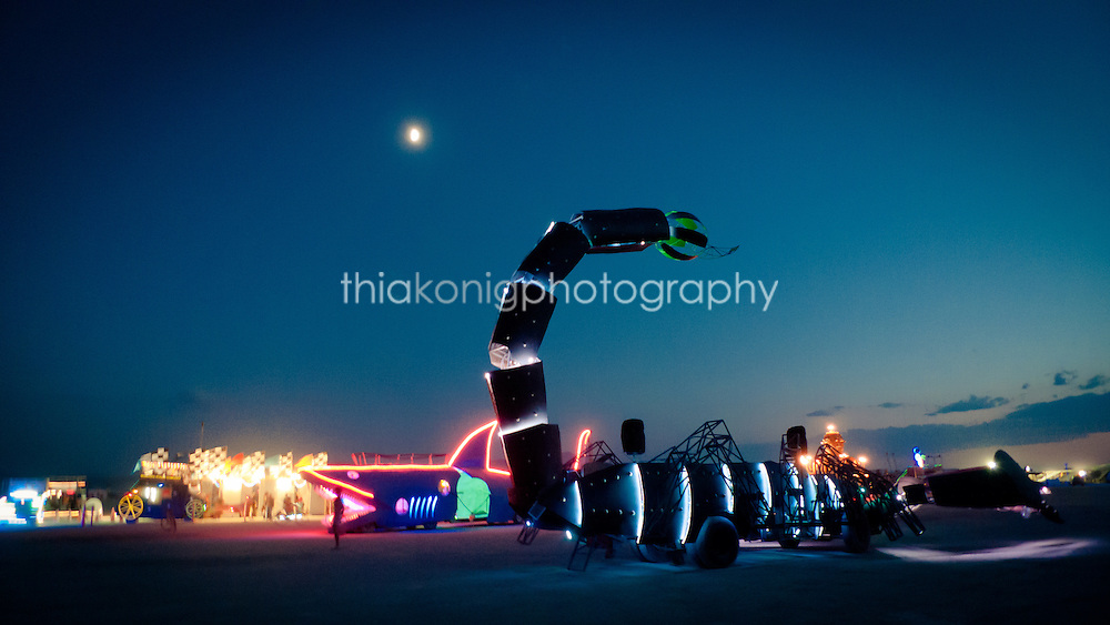 Art cars line up for the DMV at night under the full moon, including a shark and a scorpion car, at Burning Man Festival in the Black Rock desert, NV.