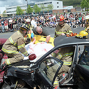 Livingston County Coroner Robert Waltman works with members of the Dansville Fire Department to remove the victim played by Noel Manly during Thursday's mock MVA held for the Seniors and Juniors of Dansville as a safety message with prom just days away. The Mock MVA show's the effects of drunk driving following a two vehicle crash following prom with first responders treating multiple injuries along with one fatality
