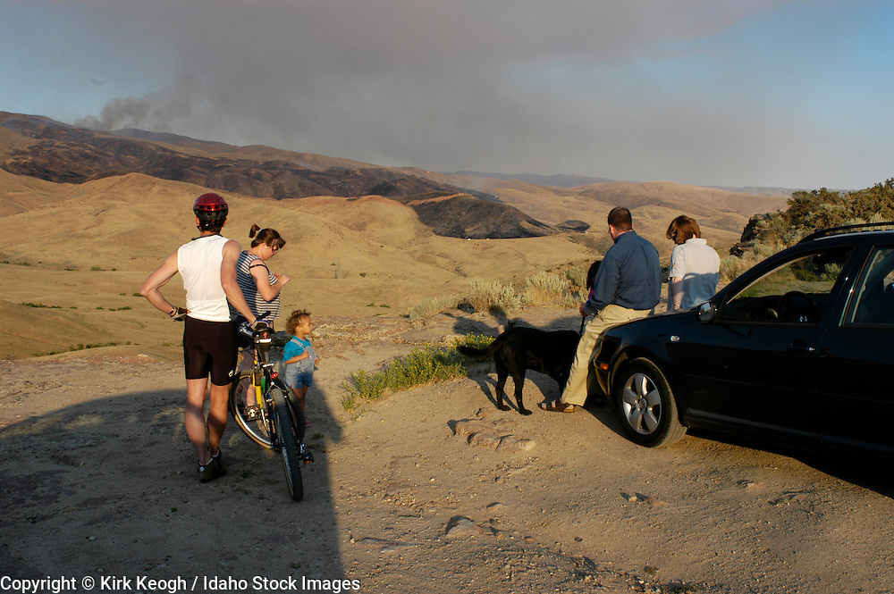 july 26, 2005.homestead fire, boise foothills, boise, idaho..people, bike rider, child, dog, adults sitting on car watching fire from table rock. foothills visible with vegetation and black. smoke and blue sky in background. Editorial Use Only.