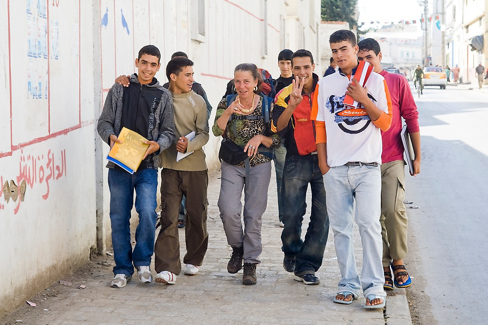 Young moroccan men, out of school for the afternoon, socialize with Liana Welty, an American tourist, on the sidewalk in Ouezzane, Morocco.