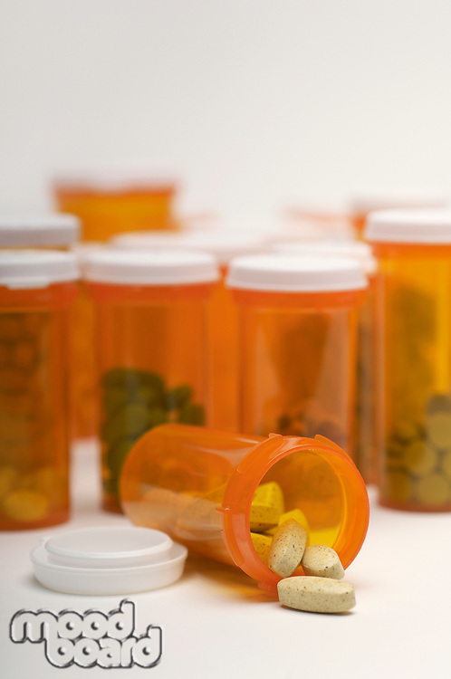 Bottles of pills, one spilling, close-up