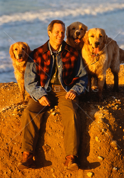Man smiling while sitting on a cliff by the ocean with three golden retriever dogs.