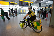 "NHS Paramedic Janet Greenhead cycles through the departures concourse on her Specialized Rockhopper mountain bike in Heathrow Airport's Terminal 5. Janet is a Responder with the cycle response unit (CRU), a part of the London Ambulance Service whose job it is to attend injuries within Heathrow's terminals. Pedalling the heavy bike laden with 55kg of medical emergency equipment she answers the calls from those with a cut finger, a baggage handler who's injured an arm, a child who's fallen over with cuts and bruises or a much more serious incident like a cardiac arrest which are common in an airport where passengers feel under stress or who forget to take their medicines while jet lagged. During a busy shift, she could end up cycling more than eight miles. From writer Alain de Botton's book project ""A Week at the Airport: A Heathrow Diary"" (2009). ."