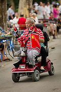 An elderly man is a handicapped scooter in Fuxing Park Shanghai, China