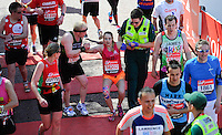 An athlete receives help at the finish line<br /> The Virgin Money London Marathon 2014<br /> 13 April 2014<br /> Photo: Javier Garcia/Virgin Money London Marathon<br /> media@london-marathon.co.uk