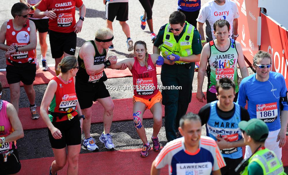 An athlete receives help at the finish line<br /> The Virgin Money London Marathon 2014<br /> 13 April 2014<br /> Photo: Javier Garcia/Virgin Money London Marathon<br /> media@london-marathon.co.uk