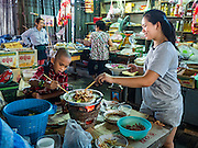 31 DECEMBER 2015 - BANGKOK, THAILAND: A woman and her son eat lunch in Bang Chak Market. The market is supposed to close permanently on Dec 31, 2015. The Bang Chak Market serves the community around Sois 91-97 on Sukhumvit Road in the Bangkok suburbs. About half of the market has been torn down. Bangkok city authorities put up notices in late November that the market would be closed by January 1, 2016 and redevelopment would start shortly after that. Market vendors said condominiums are being built on the land.          PHOTO BY JACK KURTZ
