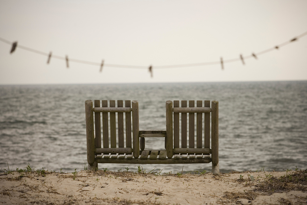wooden beach chairs facing the ocean on Cape Cod.
