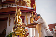 12 APRIL 2013 - BANGKOK, THAILAND: Bangkok Governor Sukhumbhand Paribatra bathes the Phra Buddha Sihing in scented oils during the start of Bangkok's Songkran observances. The Phra Buddha Sihing, a revered statue of the Buddha, is carried by truck through the streets of Bangkok so people can make offerings and bathe it in scented oils. Songkran is celebrated in Thailand as the traditional New Year's Day from 13 to 16 April. The date of the festival was originally set by astrological calculation, but it is now fixed. If the days fall on a weekend, the missed days are taken on the weekdays immediately following. Songkran is in the hottest time of the year in Thailand, at the end of the dry season and provides an excuse for people to cool off in friendly water fights that take place throughout the country. The traditional Thai New Year has been a national holiday since 1940, when Thailand moved the first day of the year to January 1. The first day of the holiday period is generally the most devout and many people go to temples to make merit and offer prayers for the new year.  .  PHOTO BY JACK KURTZ