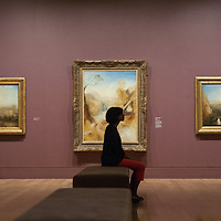 London, UK - 8 September 2014: a gallery assistant poses in front of  'The Death of Actaeon, with a Distant View of Montjovet, Val D'Aosta, c 1837' by J.M.W. Turner, during the press preview of The EY Exhibition: Late Turner – Painting Set Free exhibition at Tate Britain