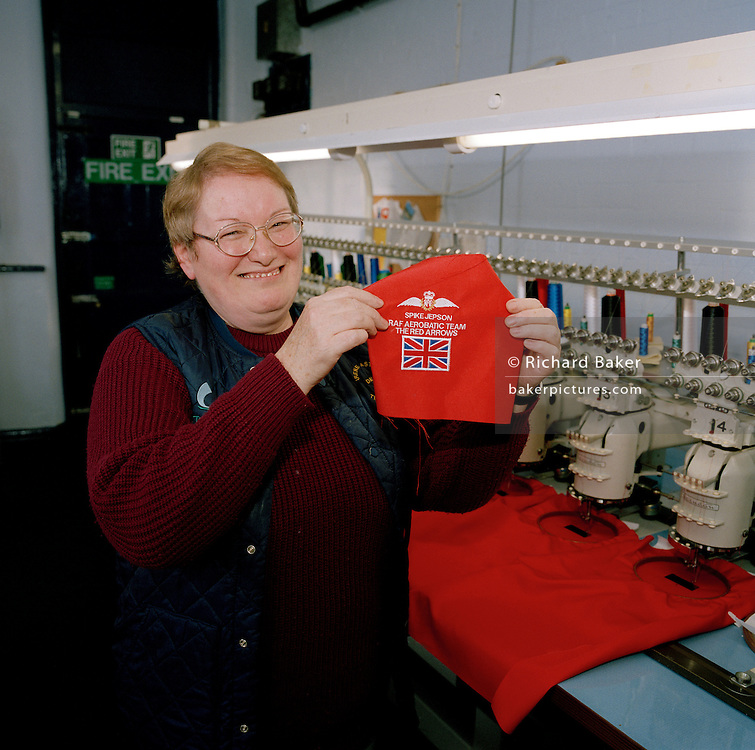 Automated stitching machinist works on badges for the elite 'Red Arrows', Britain's prestigious Royal Air Force aerobatic team at Dale Techniche, Nelson, Lancashire. Every Winter, the Red Arrows place about 40 pilot suit orders and 180 blue (support ground crew) suits. Tricia adjusts her thread while the suit is complete on her work bench. The clothing factory also designs the Red Arrows badges, each requiring 15,000 stitches. All suits are made from Nomex by the Du Pont corporation, containing 5% Kevlar. Flame-retardant, they fit exactly each team member. Fouteen different measurements are taken before the first suit is cut, each one requiring approximately three metres of dyed cloth. When a suit is complete, each one is signed inside by the machinist.