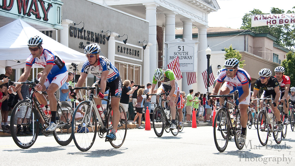 The main pack in the 2010 Bob Riccio Tour De Pitman cross the finish line in front of Broadway theatre in downtown Pitman, NJ.