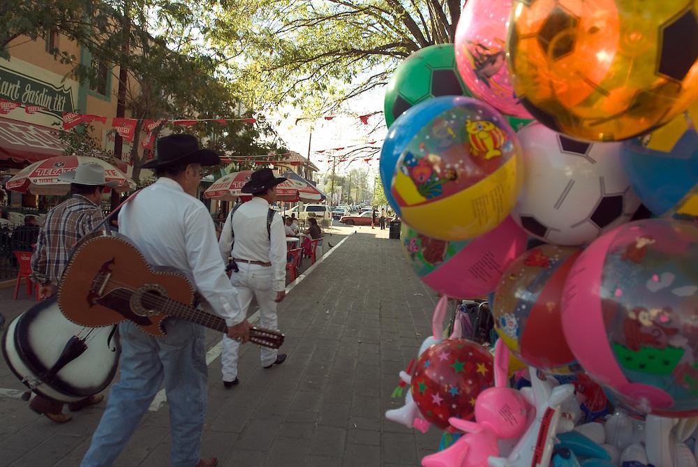 Street musicians walking along street in Tecate, Mexico