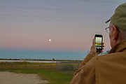 Gary Clark photographing the moon at dusk with an iPhone at Katy Prairie, in west Harris County, Texas.