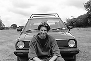 Portrait of a young Matt Smith sitting in front of his  VW Golf. Glastonbury. 1989.