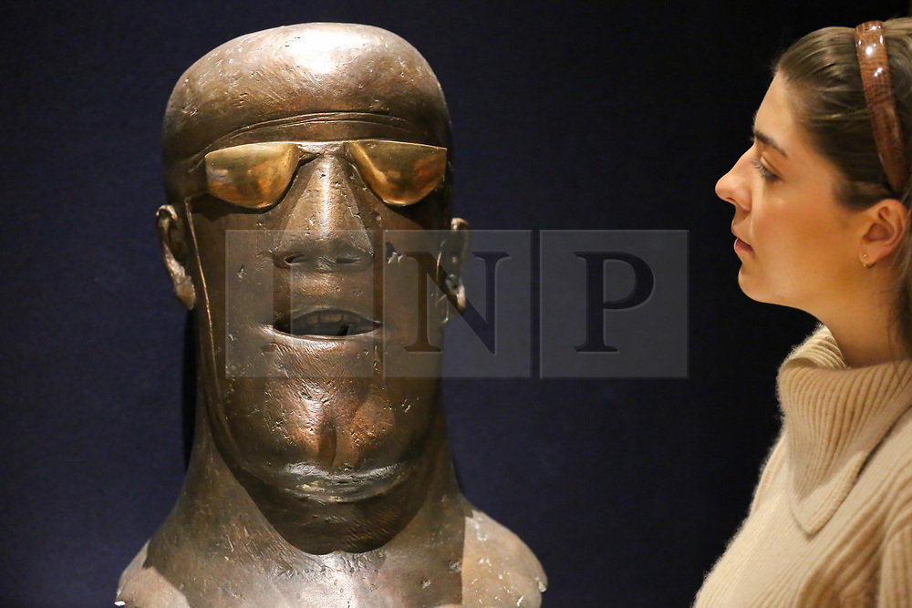 """© Licensed to London News Pictures. 12/11/2018. London, UK. A member of staff looks at """"Head"""", conceived in 1967 by Dame Elisabeth Frink R.A. (British, 1930-1993) signed and numbered 'Frink 3/6' (at the base of the neck)<br /> bronze with a brown patina and polished goggles - (Estimate £100,000-150,000).<br /> <br /> Bonhams Modern British and Irish Art photocall. Auction to be held on 14 November 2018. Photo credit: Dinendra Haria/LNP"""