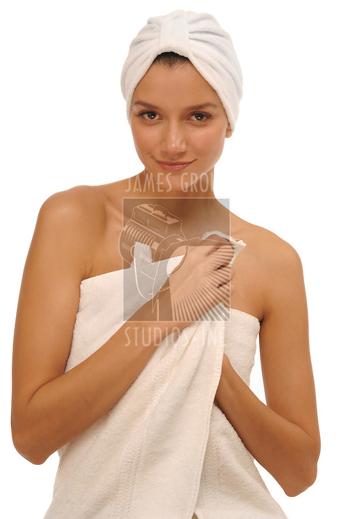 Beautiful young woman in white terry cloth towel and white spa turban on a white background