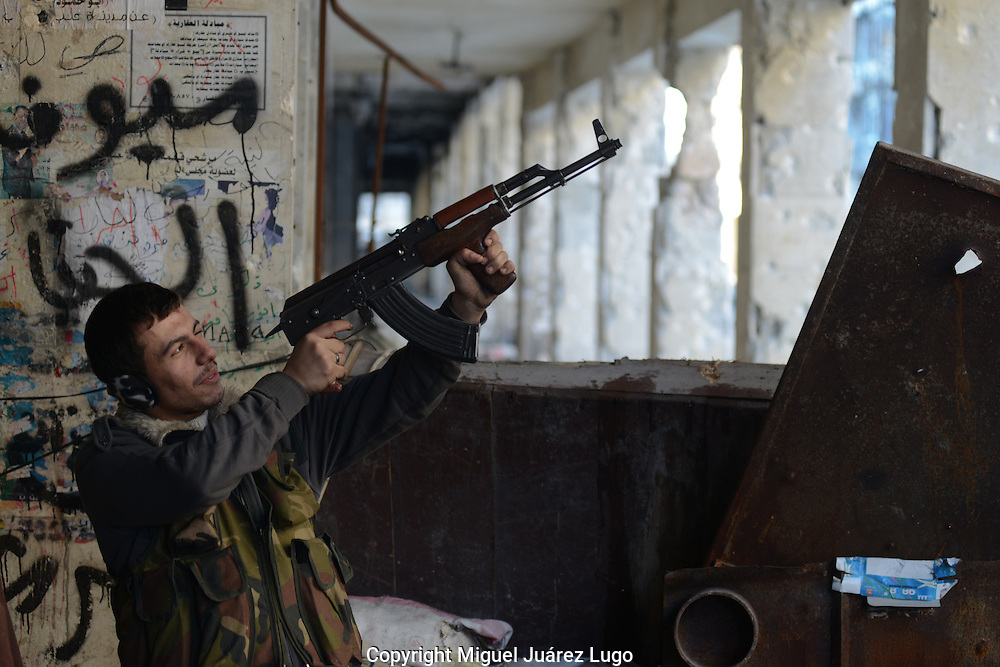 Aleppo, Syria, January, 2013 - MAHMUD, a tailor who joined the Free Syrian Army rebels, aims at a Syrian Army post from his position along Sabe'a-Bhrat Street. (Photo by Miguel Juárez Lugo)
