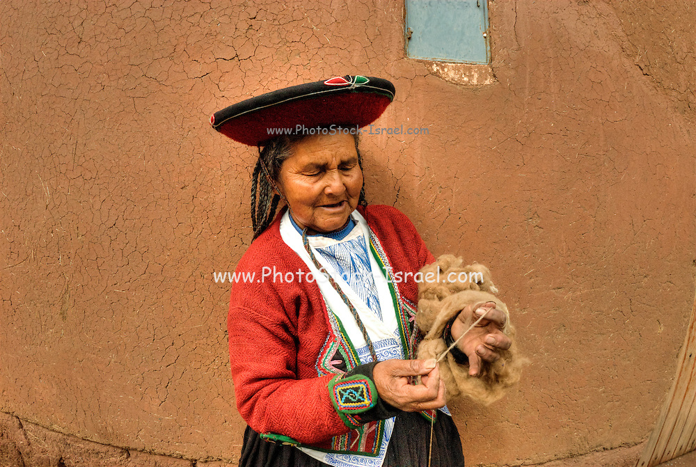 Peru, indigenous woman spinning wool with a hand spindle