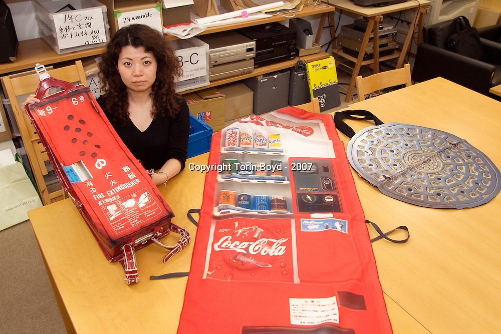 This is Aya Tsukioka, a very imaginative clothing designer who teaches at Musashino Art University on the outskirts of Tokyo. She is seen here with her creations of garments and accessories that can be quickly converted to mimic street objects. This includes a dress that can be made to look like the facade of a coke vending machine, a child's school backpack that can look like a Japanese fire hydrant, and a pouch that looks like a manhole cover for concealing items. Tsukioka's creations are based on camouflage and security if the need arises. She is seen here at her university showing her designs.