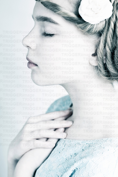 Profile of young teenage female with eyes closed and hands on on heart