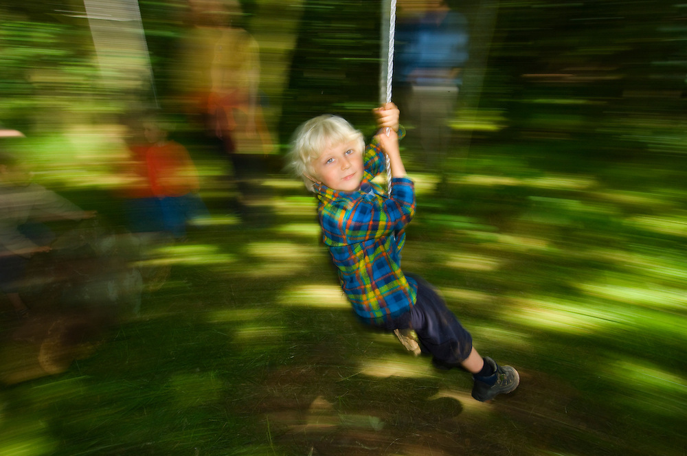 Young boy swinging through the forest